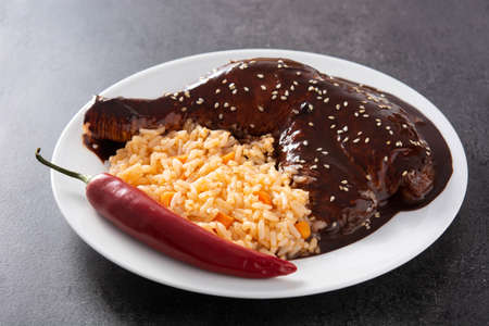 Traditional mole Poblano with rice in plate on black slate background