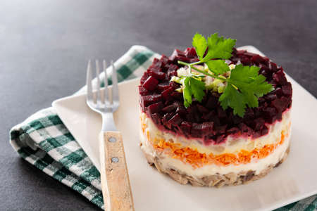 Traditional Russian herring salad with beetroot and carrots on black background Stockfoto