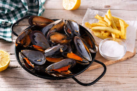 Moussels and french fries or molues-frites. Typical Belgian food. Stock Photo