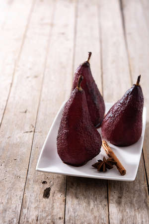 Poached pears in red wine on white wooden table. Banque d'images