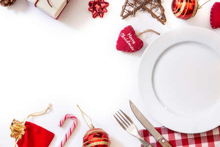 Empty white plate and Christmas ornament isolated on white background Christmas dinner concept.