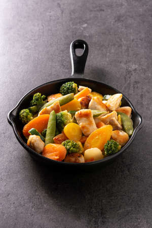 Stir fry chicken with vegetables on iron pan on black background