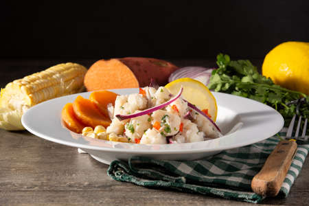 Traditional peruvian ceviche with fish, sweet potato, corn and vegetables on wooden table