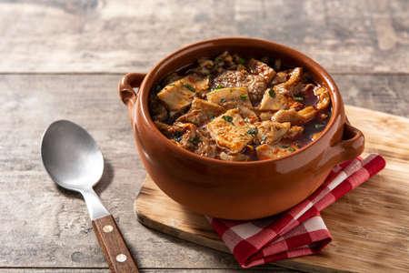 Traditional mondongo or el menudo soup on wooden table Standard-Bild