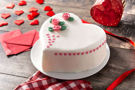 Heart cake for St. Valentine's Day, Mother's Day, or Birthday, decorated with roses and pink sugar hearts on wooden table.