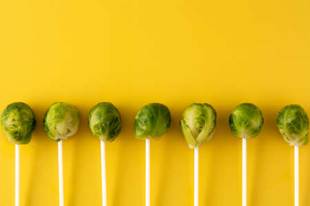 Set of brussel sprouts with lollipop sticks on yellow background