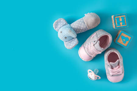 Baby shoes, pacifier and toys on blue background