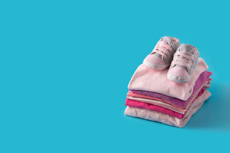 Baby rompers and baby shoes on blue background Standard-Bild