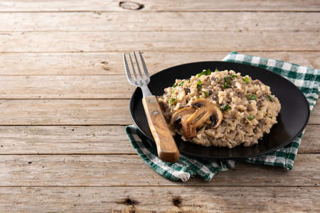 Risotto with mushroom on wooden table. Copy space