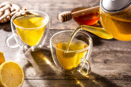 Pouring ginger tea with lemon and honey in a cup