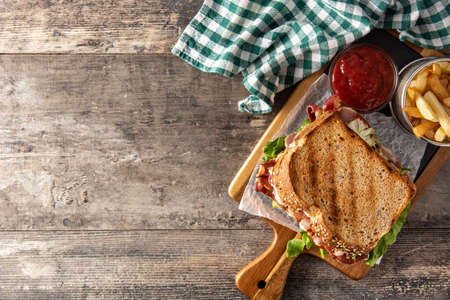 BLT sandwich with bacon, lettuce and tomato on wooden table.Top view.Copy space