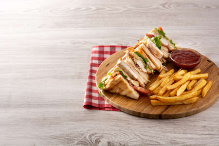 Club sandwich and French fries on wooden table