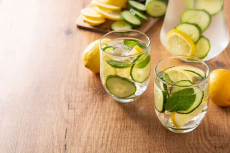 Sassy water or water with cucumber, lemon and mint on wooden table