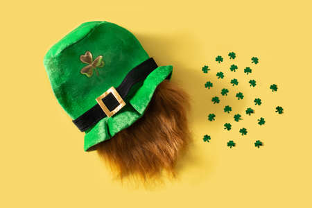 St Patrick Day hat and clovers on yellow background Standard-Bild