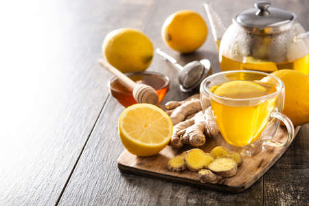 Ginger tea with lemon and honey in crystal glass on wooden table.Copy space
