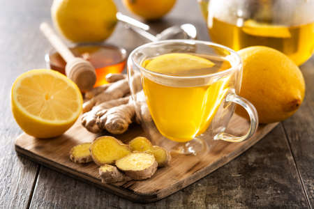 Ginger tea with lemon and honey in crystal glass on wooden table
