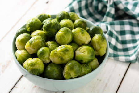 Set of brussel sprouts in a bowl on white wooden table