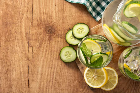 Sassy water or water with cucumber and lemon on wooden table