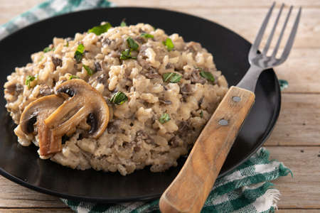 Risotto with mushroom on black plate on wooden table