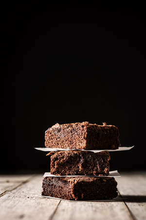 Homemade pieces of brownies on wooden table and black background