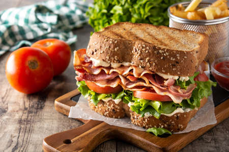 BLT sandwich with bacon, lettuce and tomato on wooden table