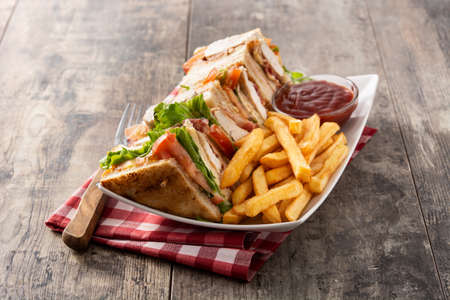 Club sandwich and French fries with ketchup sauce on wooden table