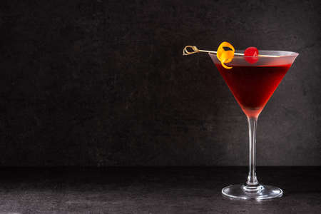 Traditional Manhattan cocktail with cherry on black background
