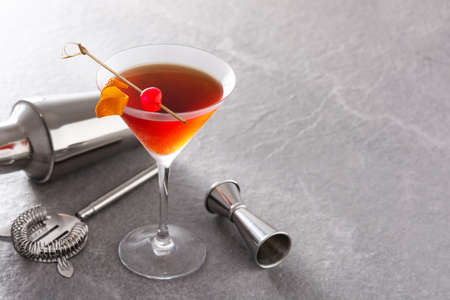Traditional Manhattan cocktail with cherry on gray stone background