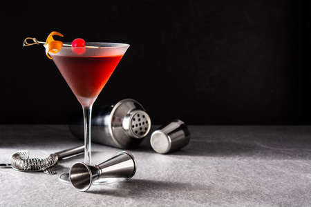 Traditional Manhattan cocktail with cherry on black slate background