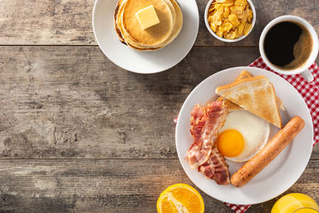 Traditional American breakfast with fried egg, toast, bacon and sausage on wooden table