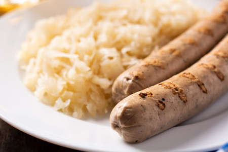 Bratwurst sausage and sauerkraut on wooden table