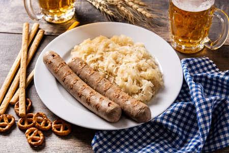 Bratwurst sausage, sauerkraut, pretzels and beer on wooden table