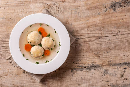 Traditional Jewish matzah ball soup on wooden table
