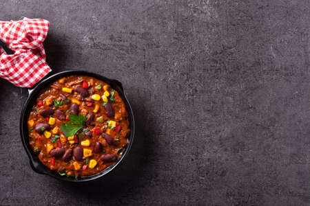 Traditional mexican tex mex chili con carne in iron pan on black stone background 版權商用圖片