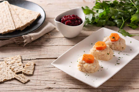 Traditional Jewish gefilte fish with beetroot and matzah bread on wooden table