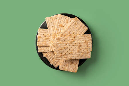 Traditional matzah bread on green background