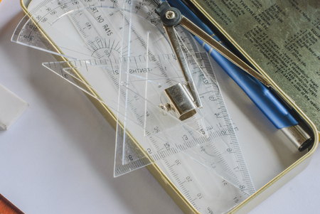 Compasses, pencil and rulers on squared paper photo