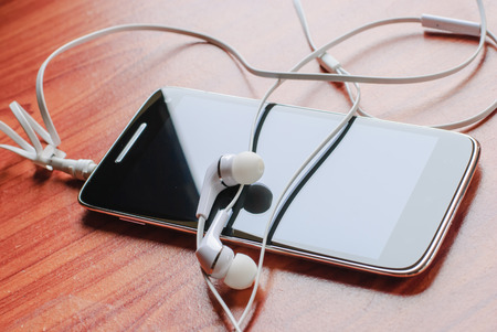 Headphones with mobile phone on wooden desk