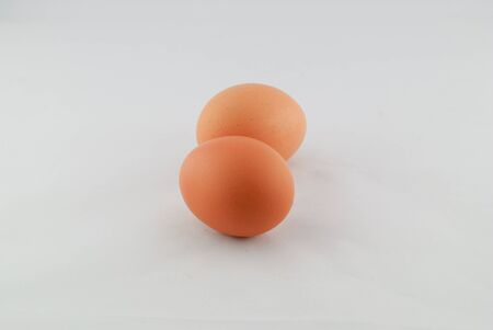 ova: two brown eggs isolated on  over white background