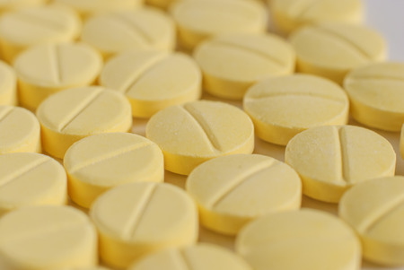 antibiotic pills: Heap of yellow  round medicine tablet antibiotic pills