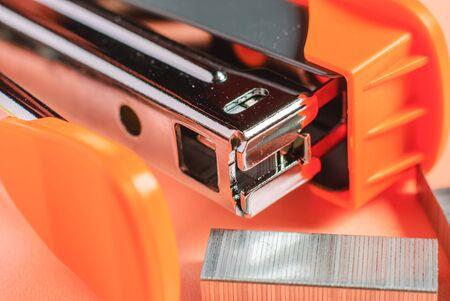 office stapler: Red office stapler isolated over red background