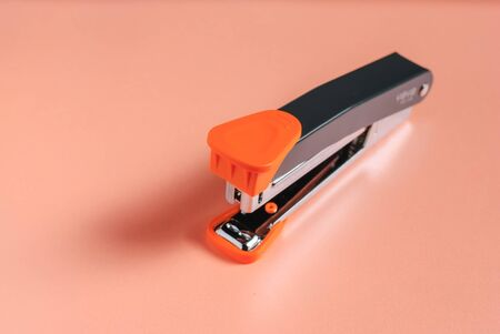 office stapler: black and red office stapler isolated over red background