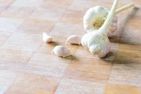 cloves: Several fresh garlic cloves on wood background. Stock Photo