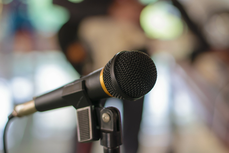 amplification: Microphone in concert hall or conference room with defocused person in background Stock Photo