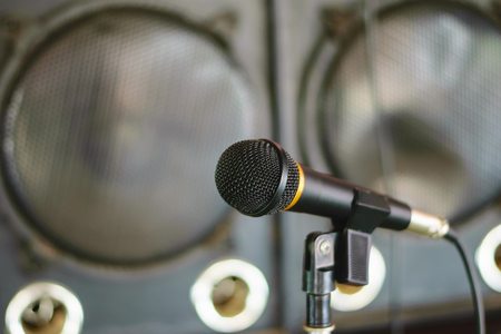 amplify: Microphone in concert hall or conference room with defocused person in background Stock Photo