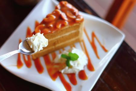 Stück Schokoladenkuchen auf einem weißen Teller auf Holz Standard-Bild