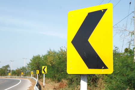 trip hazard sign: road signs indicating direction on curved road Stock Photo