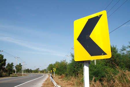 road signs indicating direction on curved road Stock Photo