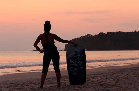 Woman surfing on the beach at sunset.