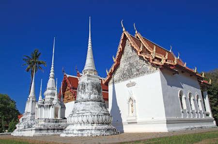 Wat Uposatharam Temple at noon under blue sky Stock Photo